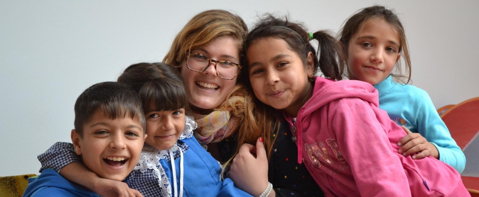 Voluntaria ayudando a niños rumanos en un centro de cuidado.